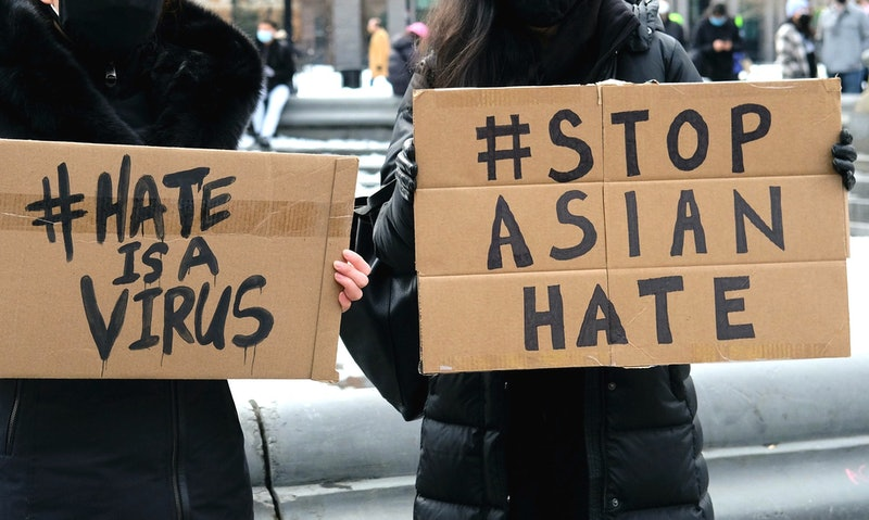 Two women hold signs saying #hateisavirus and #stopasianhate after the covid pandemic triggered a rise in anti-asian hate crimes and racism.