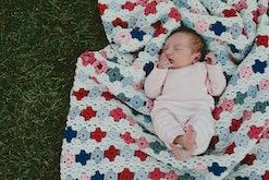 Overhead view of baby girl sleeping on blanket in yard