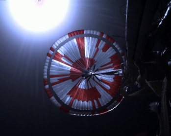 The Perseverance rover parachute seen above the rover itself as it is lowered down to the surface of Mars.