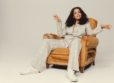'It's A Sin' star Lydia West poses in a chair wearing an all white outfit.