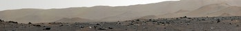 A detailed image of rocks strewn across the surface of Mars, with gradually sloping hills in the background.