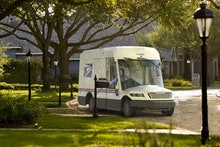 Next-generation USPS truck with large front window driving through a neighborhood.