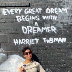 "Image of Jessica Wilson in front of a wall with a Harriet Tubman quote, ""every great dream begins with a dreamer."" Wilson, a dietitian and activist, explains how her mental health changed after gaining 100K instagram followers"