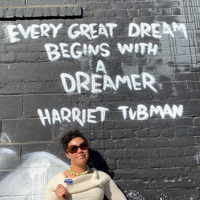 """Image of Jessica Wilson in front of a wall with a Harriet Tubman quote, """"every great dream begins with a dreamer."""" Wilson, a dietitian and activist, explains how her mental health changed after gaining 100K instagram followers"""