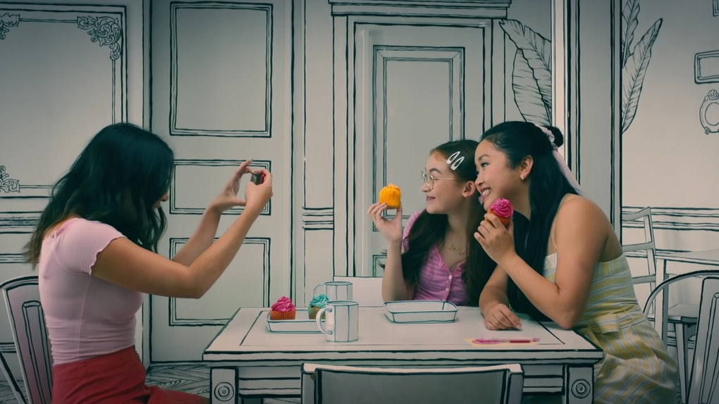 Lara Jean and her sisters pose for a picture at a 2D cafe in Korea in 'To All the Boys: Always and Forever.'