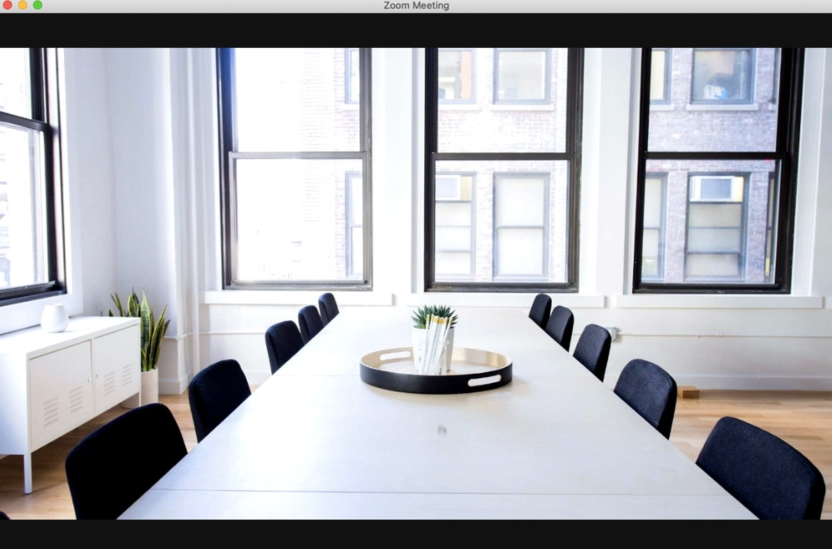 For group meetings, this office background for Zoom sets the scene with a minimalist conference room table.