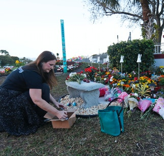 A woman places painted rocks at a memorial to those killed in the 2018 Parkland, Florida, school shooting