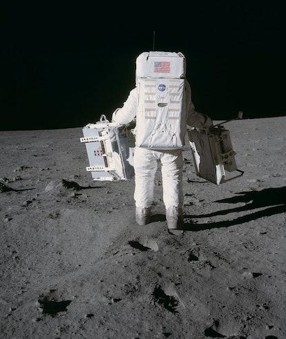 An Apollo astronaut walking across the surface of the Moon.