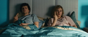 Jesse Eisenberg and Imogen Poots in a blue bed with a grey headboard, their middle fingers raised in...