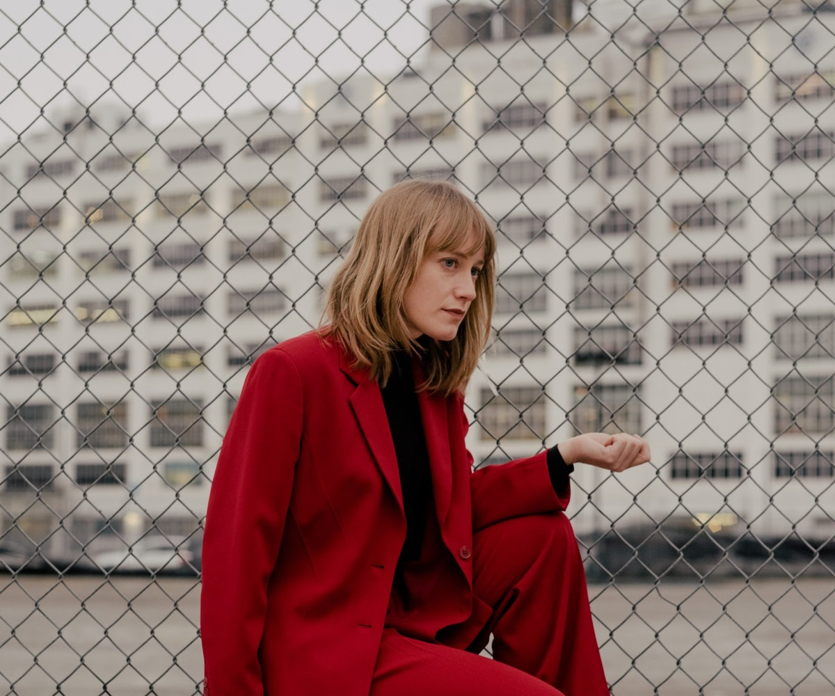 A portrait of The Weather Station's Tamara Lindeman. She's crouched in front of a wire gate in a cri...