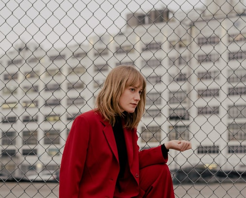 A portrait of The Weather Station's Tamara Lindeman. She's crouched in front of a wire gate in a crimson suit, looking off to the side.