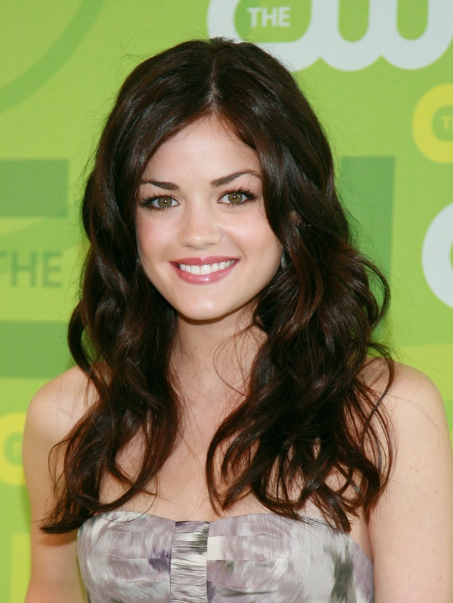 Lucy Hale, with curly hair, poses against a lime green backdrop