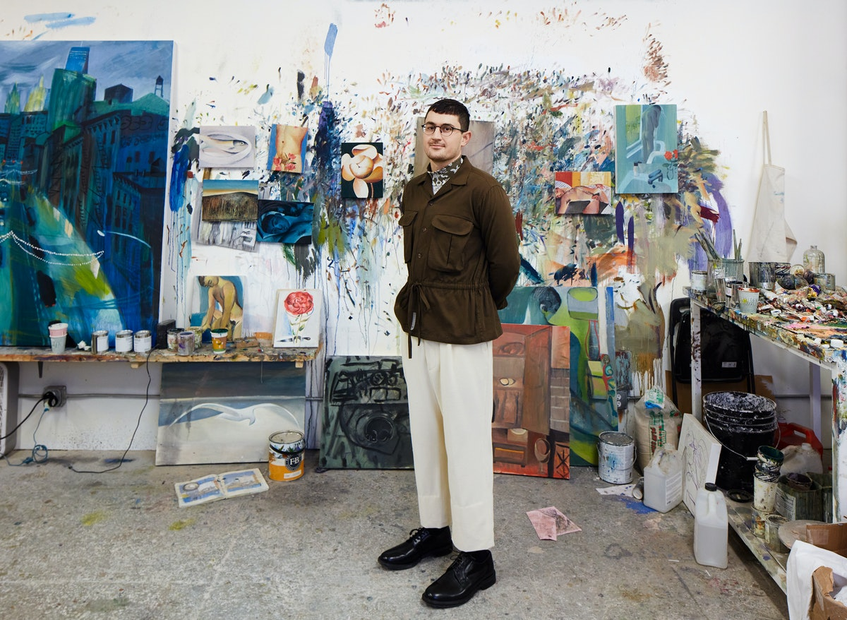 Louis Fratino in his Queens studio in front of various works in progress. Fratino wears a Connor McKnight shirt and pants; Dior Men's turtleneck; Church's shoes; his own glasses. Styled by Marion Kelly. Grooming: Remi Odunsi for R+co and Chanel Beauty; photo assistant: Janelle Jones.