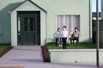 Imogen Poots, Senan Jennings, and Jesse Eisenberg on the front yard of their suburban-style 9 house.