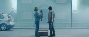 Imogen Poots, a baby, a cardboard box, and Jesse Eisenberg stand in front of a house.