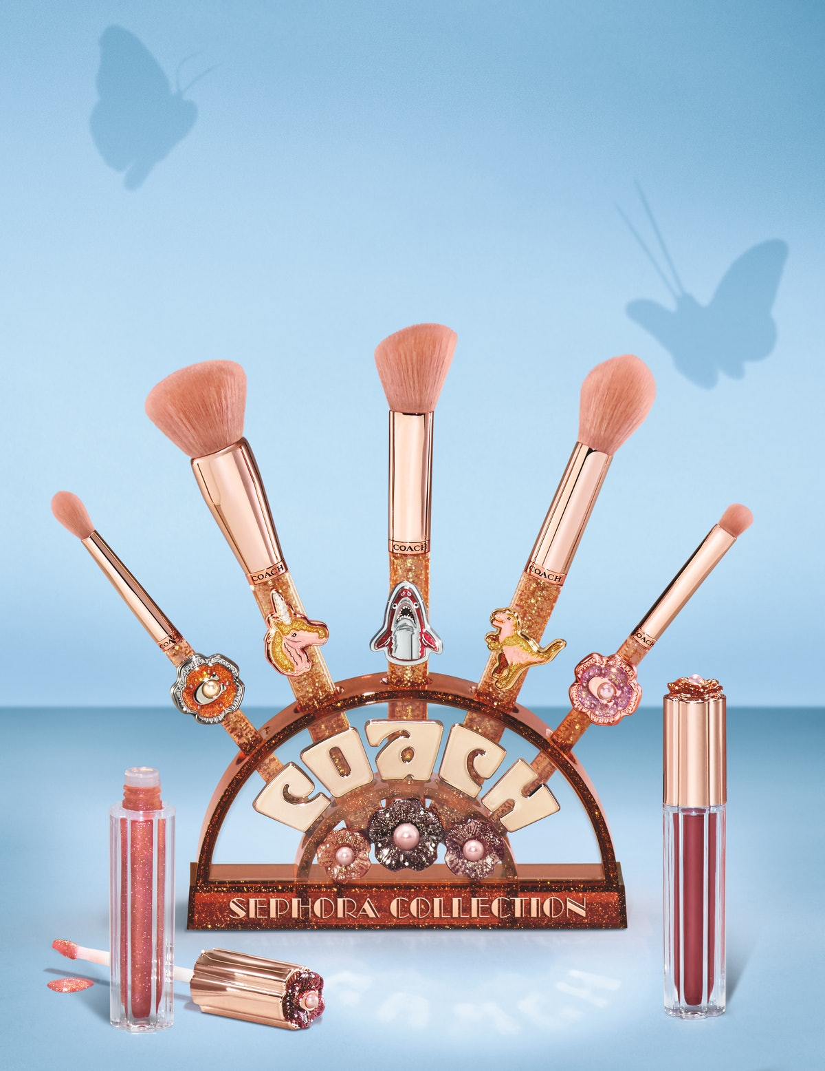 The COACH x Sephora brushes and brush stand accompanied with two of the lipglosses.