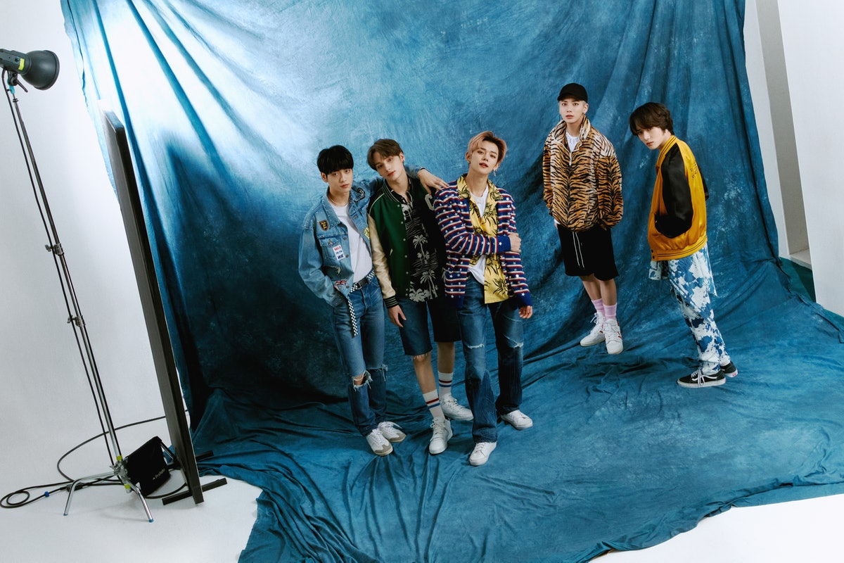 From left to right: Soobin wears Celine by Hedi Slimane jacket, jeans, belt, and shoes, stylist's own T-shirt, earrings, and necklace; Hueningkai wears Celine by Hedi Slimane jacket, shirt, socks, and shoes, stylist's own shorts and earring; Yeonjun Celine by Hedi Slimane cardigan, shirt, jeans and necklace, stylist's own T-shirt and earrings, Vans shoes; Taehyun wears Celine by Hedi Slimane jacket, necklace, and shoes, stylist's own T-shirt, shorts, hat, and earrings, Nike socks; Beomgyu wears Celine by Hedi Slimane clothing, stylist's own earring, Vans shoes