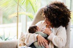 woman sitting in modern armchair, breastfeeding baby