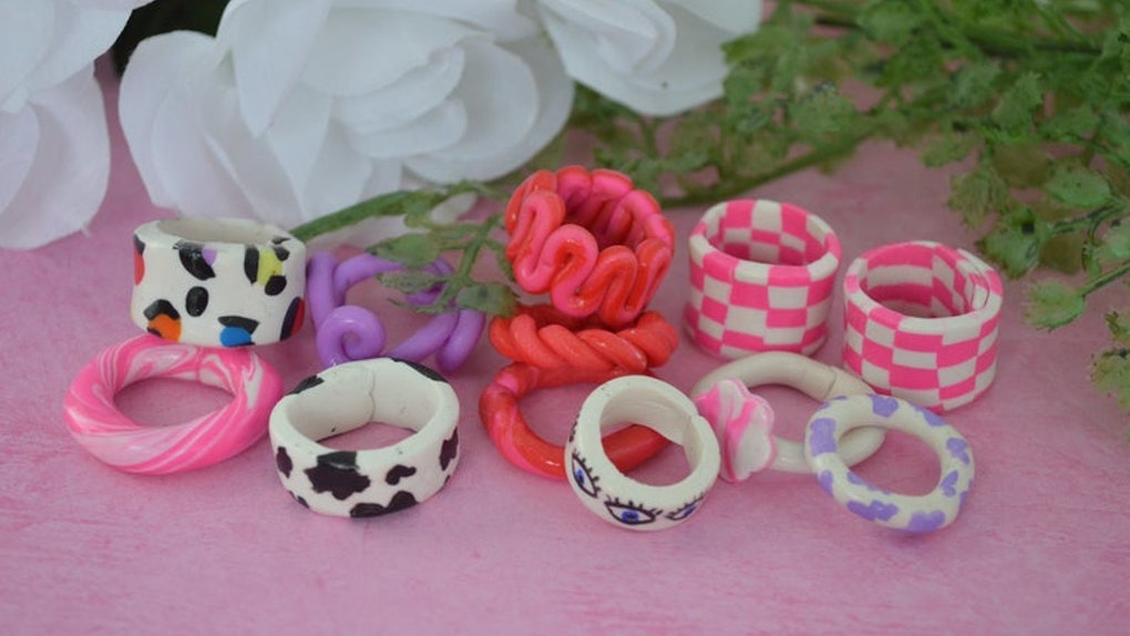 A collection of colorful and patterned chunky rings are presented on a cute pink table.
