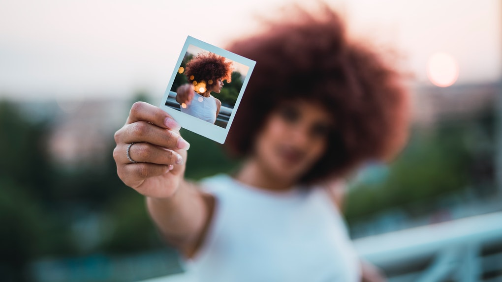 Young woman showing selfie, instant photo of herself, close-up