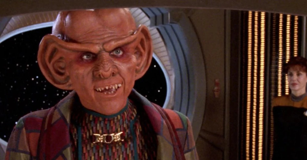 The Ferengi alien Quark, seen in colorful garb, with a Starfleet officer in the background
