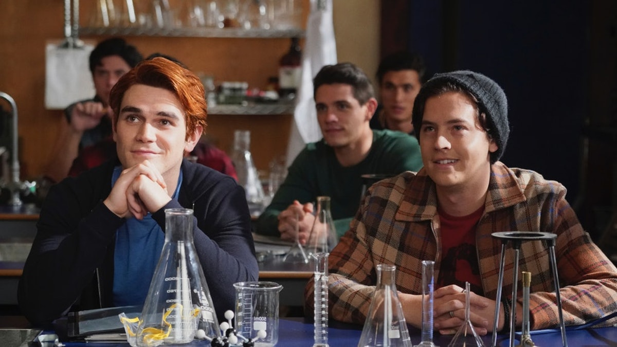 Archie and Jughead smile while sitting at a desk in science class in 'Riverdale.'