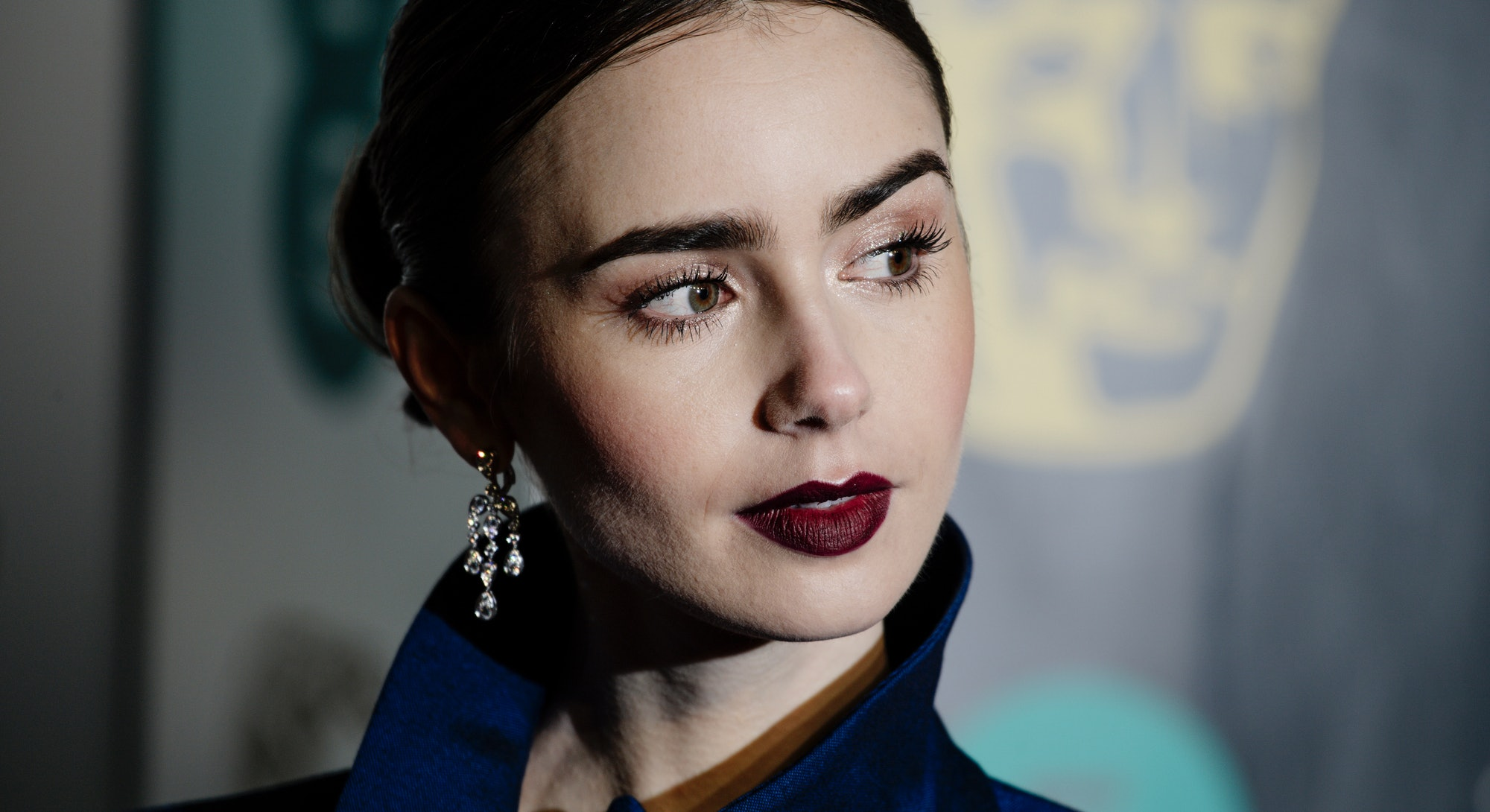 Lily Collins wears dark lipstick, along with a middle part, and her hair pulled back