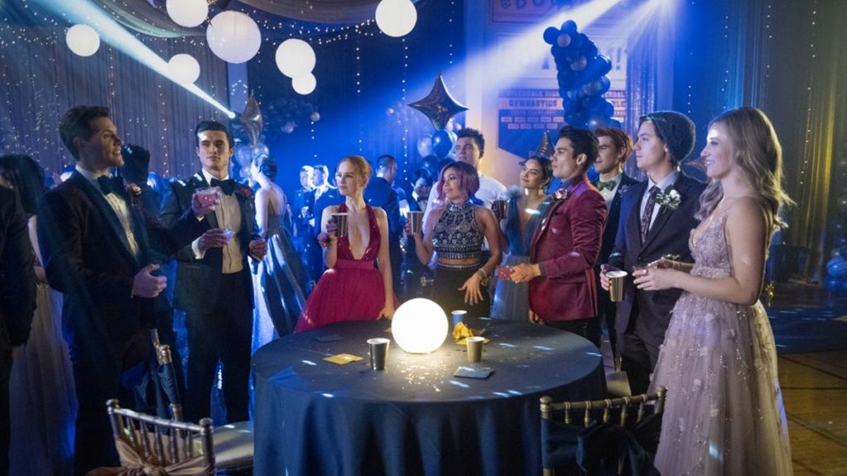 The 'Riverdale' crew gathers around a table at a school dance.