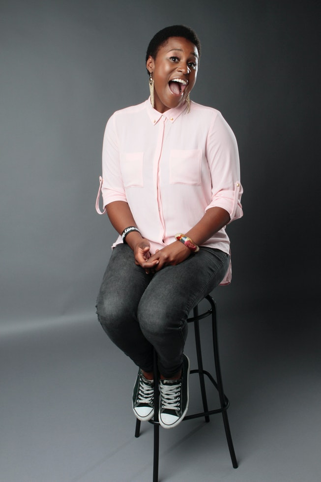 Issa Rae in a light pink button down shirt on a stool in a studio.