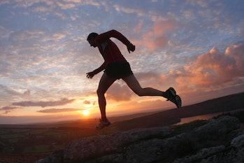 Man running across moors at sunset.