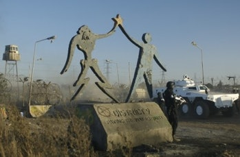 A statue from District 9 showing an alien and humand holding hands.