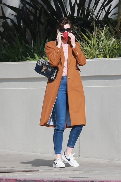 Anne Hathaway stops and switches shoes before going to a meeting in Santa Monica with husband Adam Shulman. 2/4