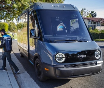 An Amazon delivery worker walks away from a Rivian electric van while holding a package