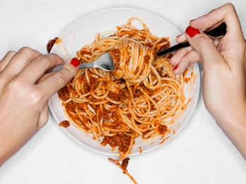 Eating a plate of pasta.
