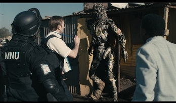 Sharlto Copley and military backup confronting an alien in a slum