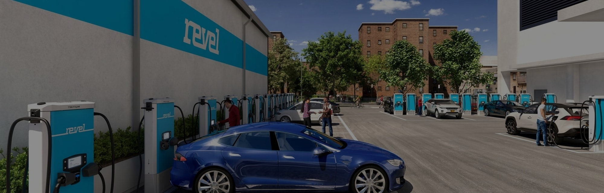 A blue Tesla sits docked at a Revel electric charging station.