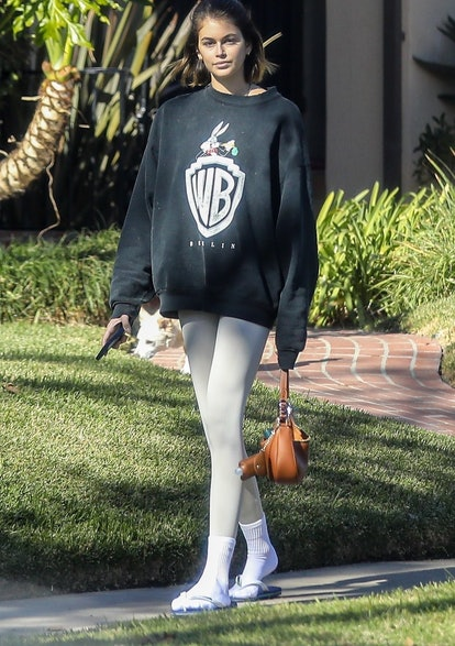 New Hollywood 'IT' couple Kaia Gerber and Jacob Elordi enjoy a walk outside with their dog in Santa Monica. Kaia and Jacob appear inseparable since first being linked together this past September. Kaia is seen wearing a Warner Brothers sweater and no make up. The young model carried a small leather handbag with a convenient pouch for her hand sanitizer.