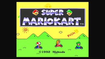 """The opening screen for Super Mario Kart, featuring from left to right Toad, Princess Peach, and Luigi against a green and yellow backdrop with """"Push B"""" graffiti"""