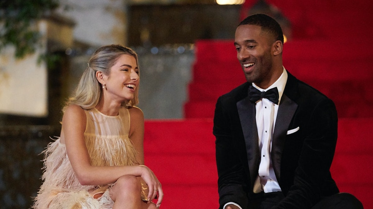 Kit and Matt James laugh while sitting on red carpet steps on 'The Bachelor.'