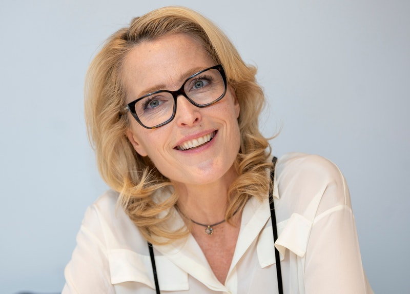 Gillian Anderson at a press junket for the crown wearing black rimmed glasses and a white shirt