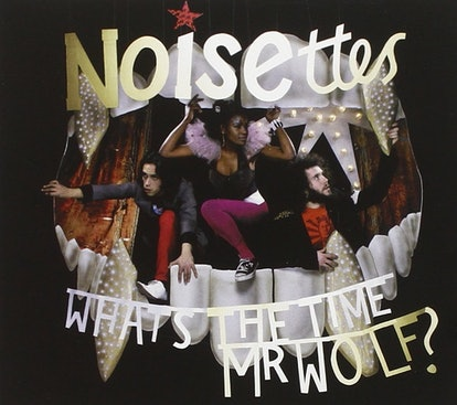 The album cover for the Noisettes' 'What's The Time Mr Wolf?' It shows the band climbing out of a giant wolf mouth stage prop.