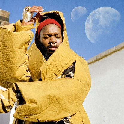 The album cover of serpentwithfeet's 'soil.' It shows serpentwithfeet wearing a big yellow coat in mid-dance, with two moons in the sky.