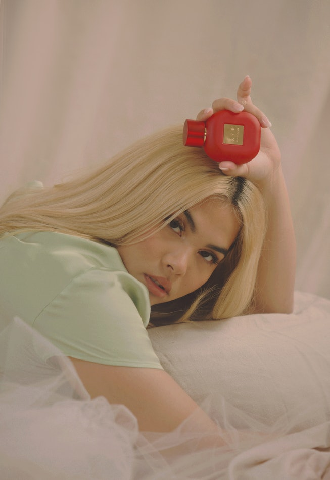 Artist Hayley Kiyoko in mint green blouse holding red bottle of perfume.