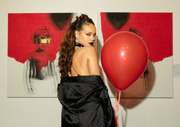 Rihanna stands against a white backdrop, wearing black lipstick