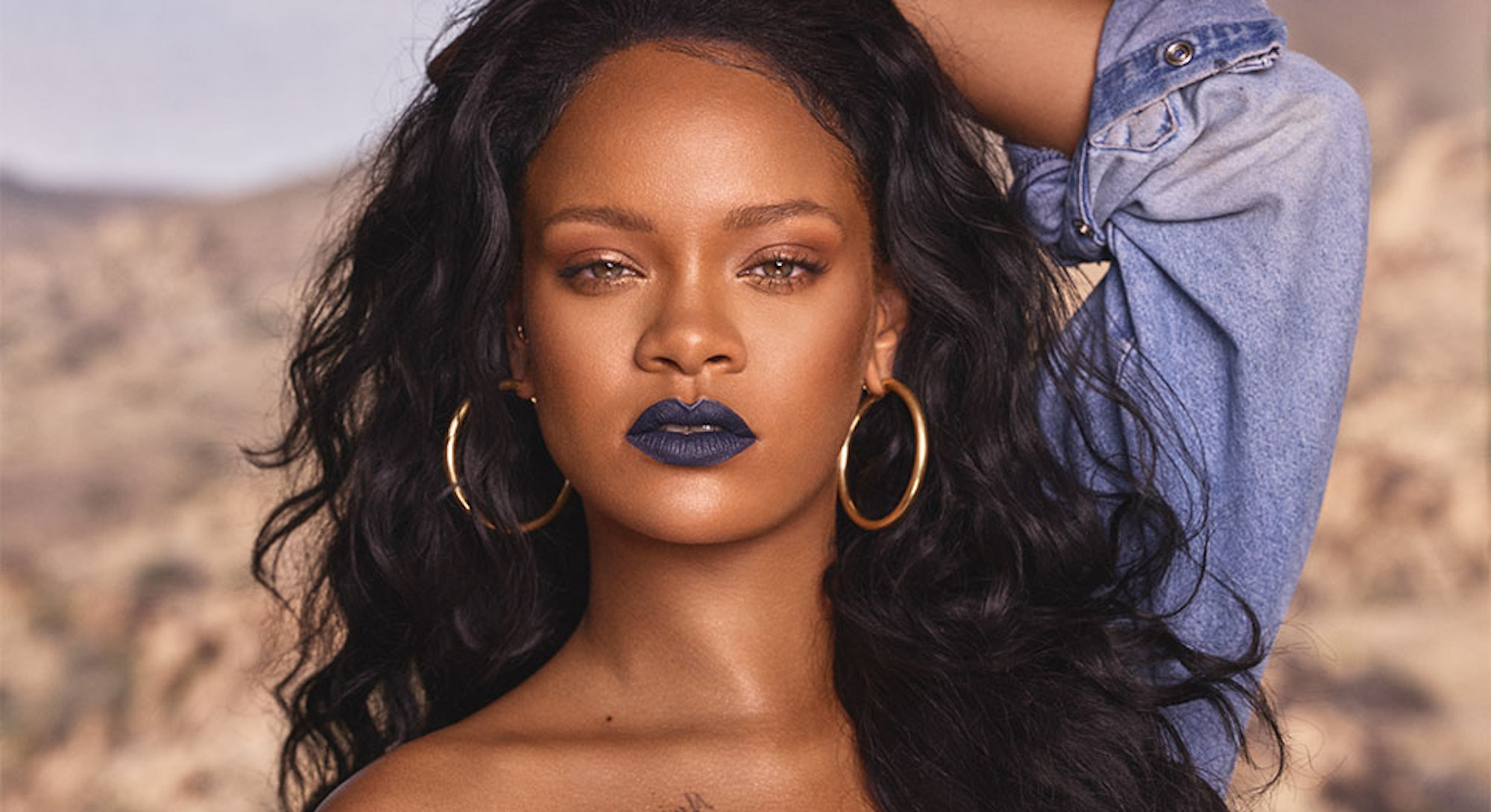 Rihanna with dark blue lipstick and gold hoop earrings for a Fenty Beauty campaign.