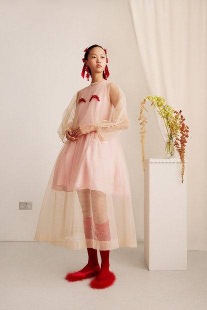 A female model wears a sheer gown from the Simone Rocha x H&M collection.