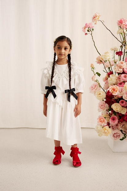 A young model wears a white dress from the childrenswear selection of the Simone Rocha x H&M collection.
