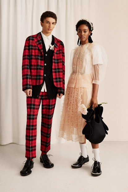 A male model wears a plaid suit and a female model wears a sheer gown from the Simone Rocha x H&M collection.