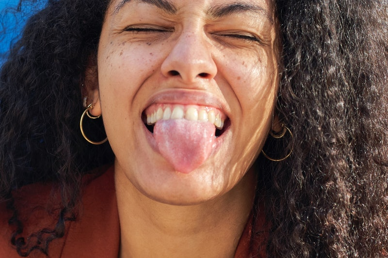 A woman sticks out her tongue close up. COVID tongue may be a sign of COVID.