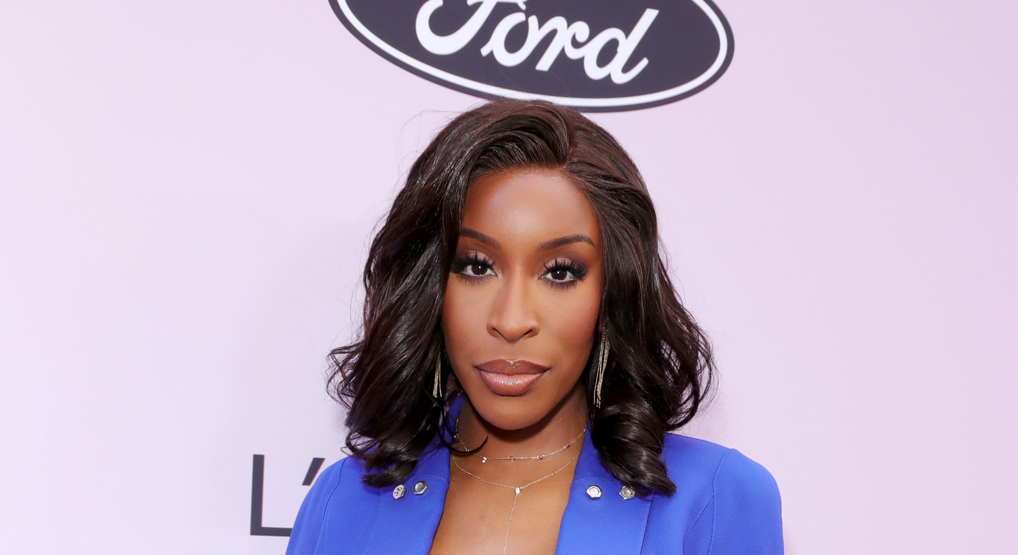 Jackie Aina on the red carpet in a blue dress with plunging neckline.